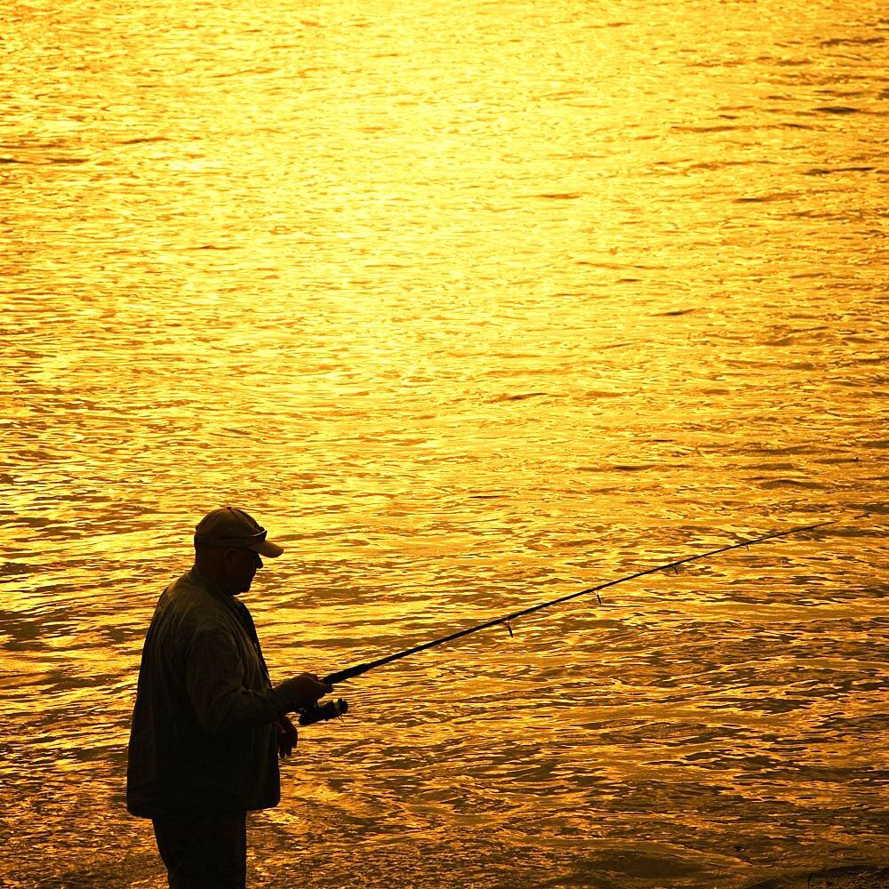 Silhouette of a man fishing from the shore in the Santa Barbara Harbor, Santa Barbara, California.