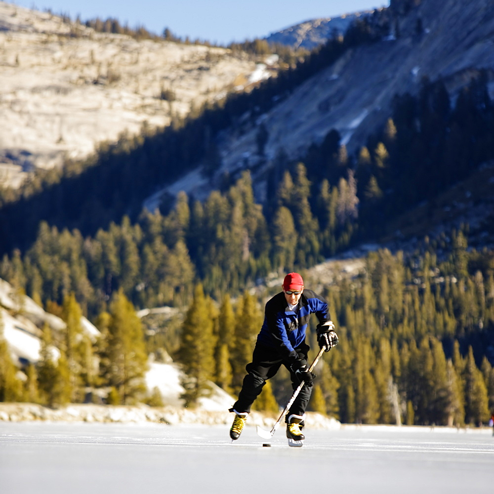 Low angle front view of a ice skater playing ice hockey on a snow free, frozen Tenaya Lake in Yosemite National Park.