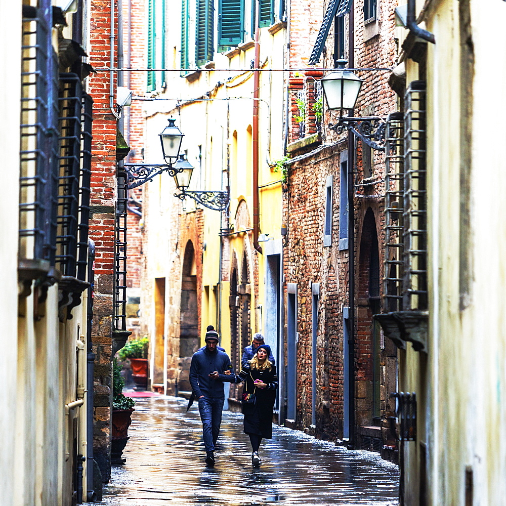 Front view of people walking the wet city streets in Lucca, a city and commune in Tuscany, Central Italy, on the Serchio, a fertile plain near the Tyrrhenian Sea. It is the capital of the Province of Lucca. It is famous for its intact Renaissance-era city walls.