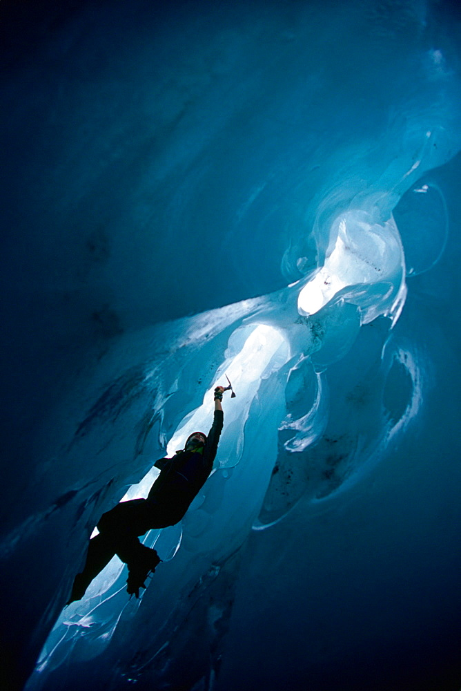 An ice climber climbs out of an ice cave on the Franz Josef Glacier on New Zealand's South Island.