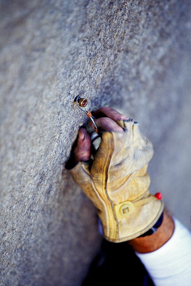 Martian Avidan rock climbing, aid climbing, big wall climbing up the Zodiac 5.13+ on El Capitan in Yosemite National Park, California. In the photo you see Avidan placing a wire rivet hanger on a rivet. The climber wears leather gloves to protect his skin from the elements. The team spent three days and two nights on the big wall. Several haul bags are visible in the photo.