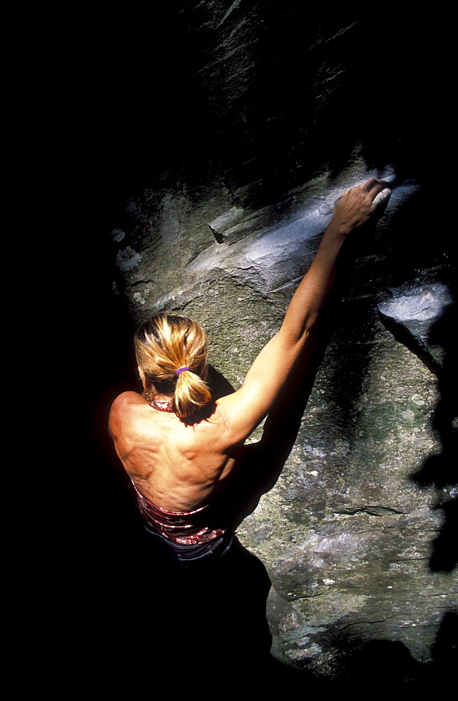 Rock climber Cassandra Riddle climbs out of the shadows while climbing at Carver, Oregon.