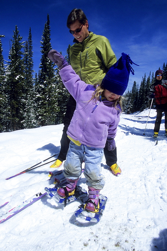 A father, Brad Piehl, watches while his daughter, Jenna, snowshoes for the first time, on the snow covered Boreas Pass Road, a popular winter recreation trail for cross country skiers and snowshoers.  The road becomes a trail, and is part of the Rails to Trails system.  It follows an old railroad grade southeast over the mountains to the town of Como.