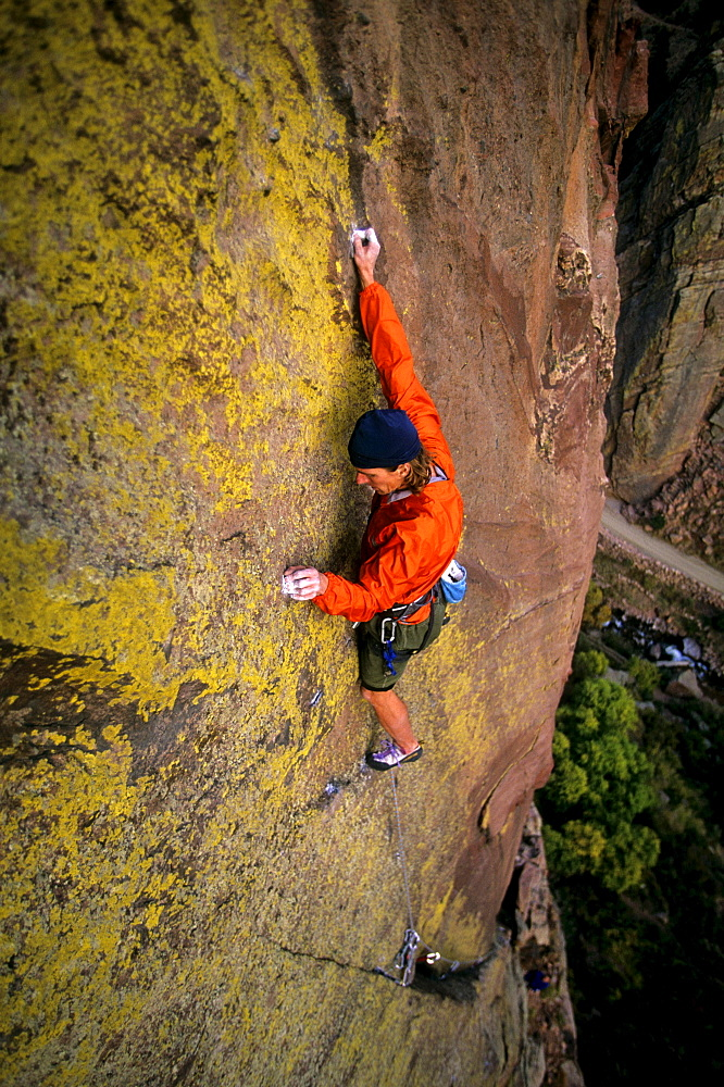 """Bruce Miller climbs on the hardest part, or """"crux"""", of a route called """"Jules Verne"""", rated 5.11a, high off the ground on the Redgarden Wall in Eldorado Canyon State Park, CO.  Jules Verne is one of the more famous traditional or """"trad"""" routes in the area, and has long sections between protection. Eldorado Canyon, located on the Front Range south of Boulder, and  its steep, difficult sandstone cliffs attract climbers from around the country and the world, making it one of  the most popular climbing areas in Colorado."""