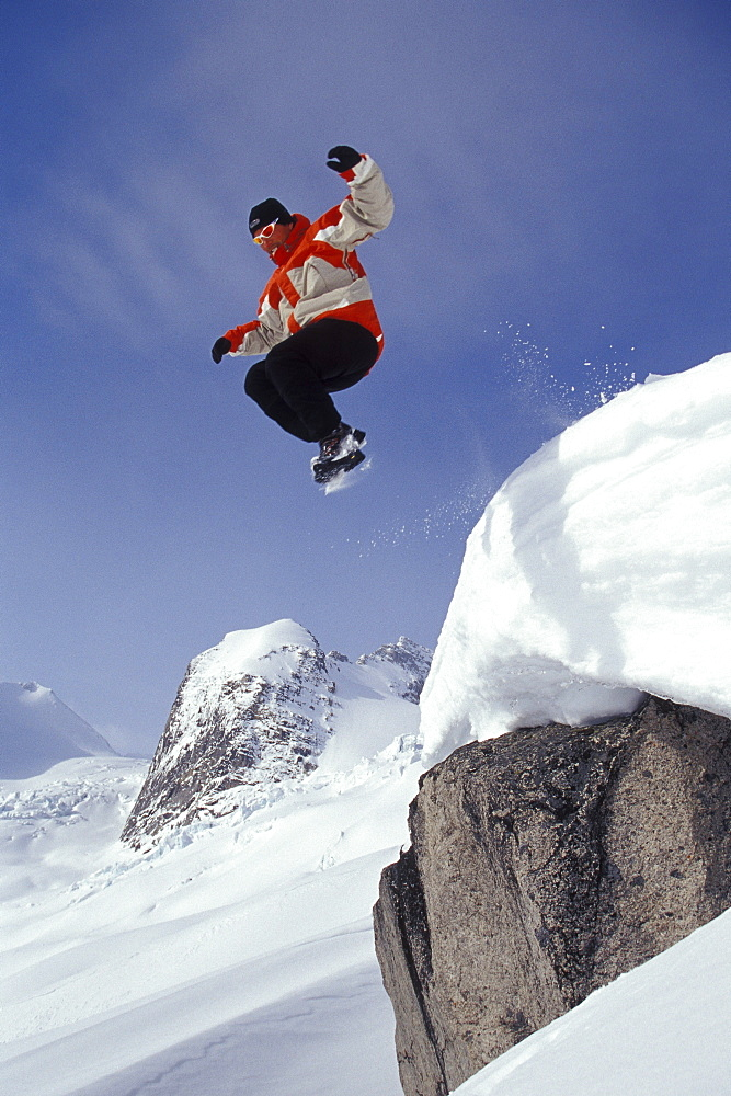 "Steve Whelan jumps off cilff into fresh snow in front of the ""Hounds Tooth"" in Bugaboo Glacier Provincial Park, near Golden, British Columbia, Canada."