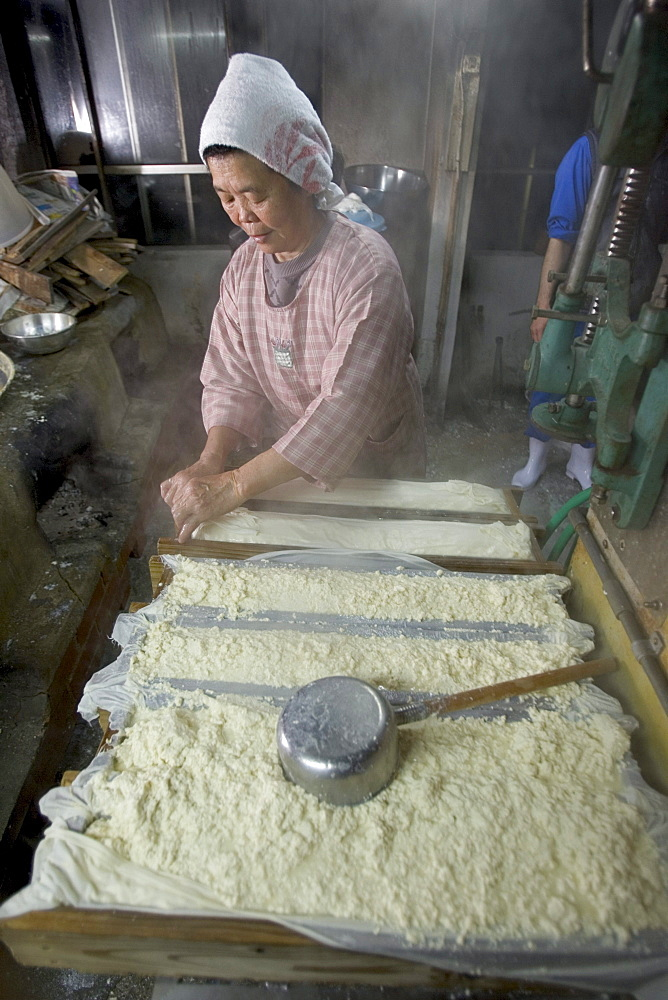 """Kazuko Uezu, age 65, makes tofu before dawn in her small shop in the village of Hedo.  Despite 50 years of practice """"every batch tastes slightly different"""" says Kazuko who rises at 4-am seven days a week to make tofu.  Traditional methods and a small production produces subtle variations in every batch despite the fact that tofu has only two ingredients, salt water and soy beans.  Kazuko get the salt water from the East China Sea (just down the road from her house) but the soybeans come from America.  Okinawan centenarians eat tofu daily and it is believed the high flavanoid content in tofu contributes to their longevity.  Flavanoids are known to fight breast and prostate cancer and believed to combat heart disease."""