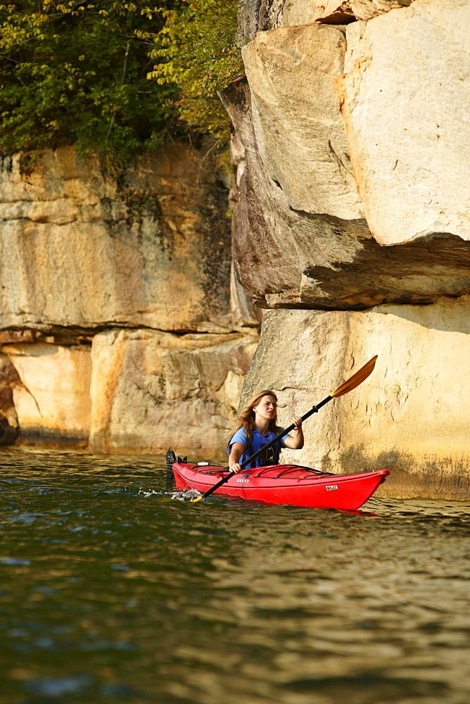 Lydia McDonald explores via sea kayak the large sandstone cliffs that line Summersville Lake near Fayetteville, WV