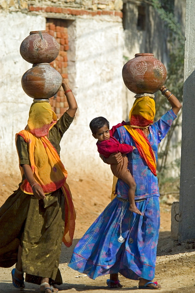 A Rajasthani woman with a burqua (veil) covering her face walks toard the village well with her young son on her hip. In Rajasthani tradition she carries her ceramic water pot balanced on her head.
