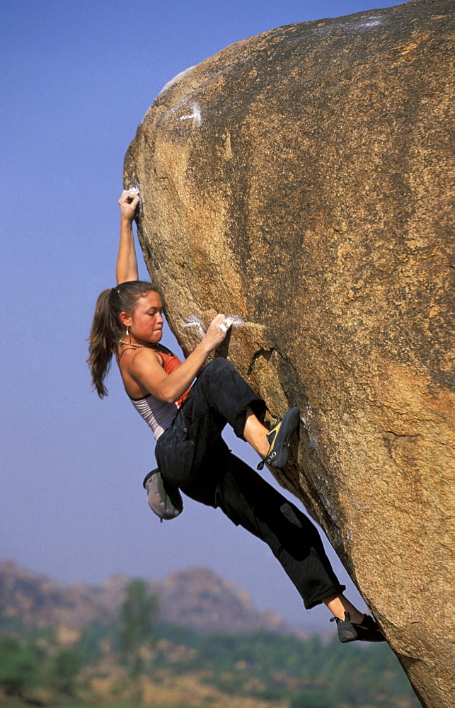 Katie Brown sucks it up as she nears the top of an overhanging bouldering route. Katie Brown, one of the world's leading sport climbers and the first  woman to flash a 5.14a sport route, is bouldering near the Hampi, ruins outside of Hampi, India.