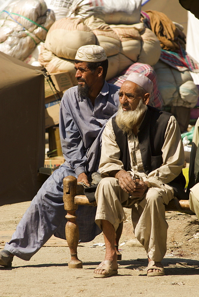 In the Meira camp for earthquake survivors, two Pashtun men sit by piles of family possesions, waiting for the truck which will take them from the camp, where they have spent the winter, back to their devastated mountain village, in the Northwest Frontier Province, Pakistan. The Pakistani army, which runs the camp, has mandated that the camps be cleared by early April, despite the fact that many families are afraid or unprepared to return to their devastated homes. The Meira Tent camp (also called Mera, or Maria camp), is located on the Indus River in the Battagram district.  The camp, the largest for displaced people in Pakistan, hosts over 21,000 earthquake survivors, primarily from the Allai valley in Pakistan's NWFP, one of the areas worst-hit by the October 8, 2005 earthquake.