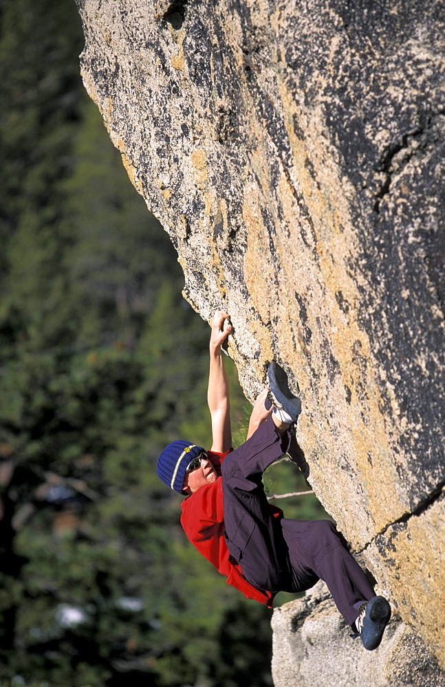 Young male rock climber Scott Corey bouldering at Echo Estates in the Sierra Nevada mountains, Lake Tahoe, California.