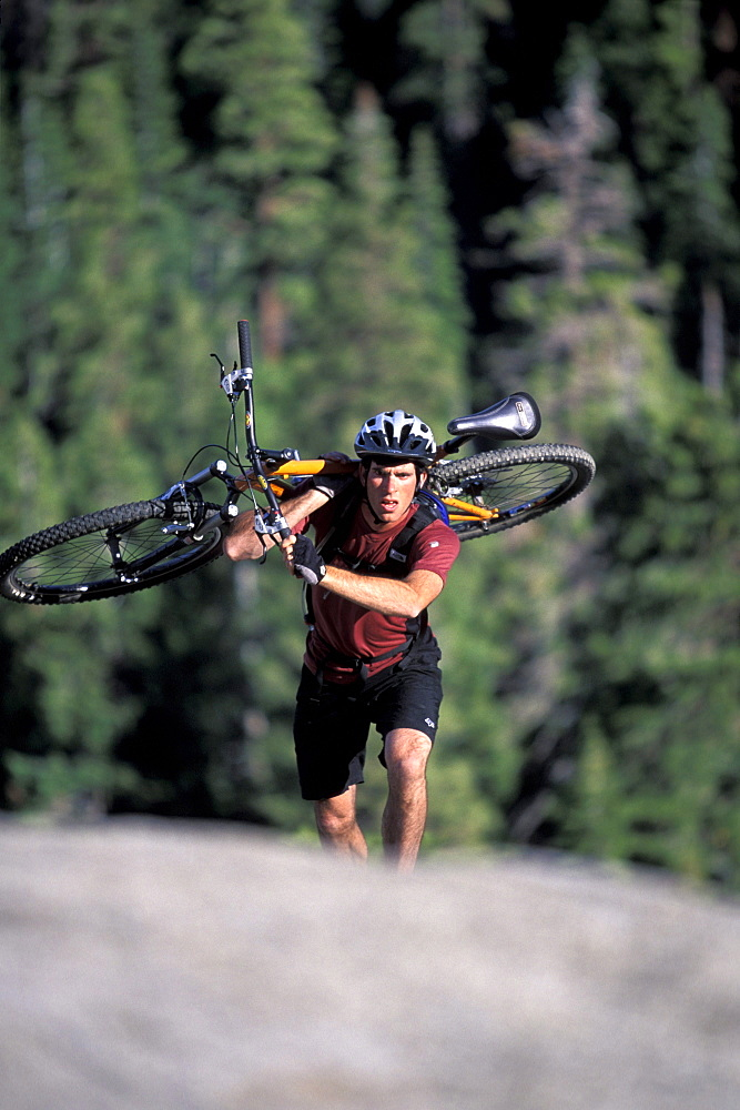 A man carrying his mountain bike up a hill in Lake Tahoe, California (Selective Focus).