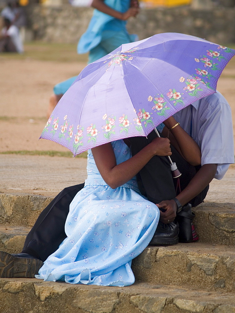 Young couples using umbrellas for privacy