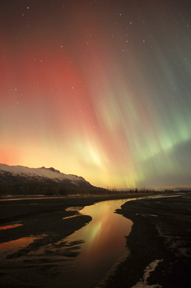 The aurora borealis (northern lights) shines with multiple colors above the Chugach Mountains in Alaska's Knik River Valley.