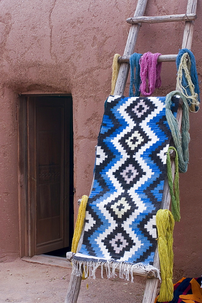 A woven mat drapped over a ladder in New Mexico.