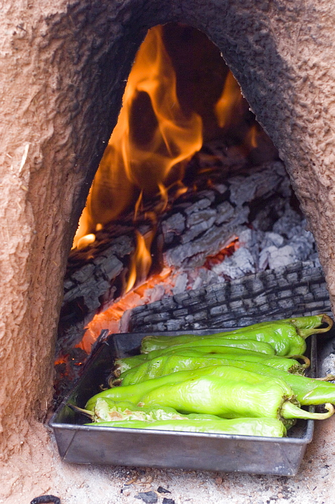 Roasting green chile in a traditional oven in New Mexico