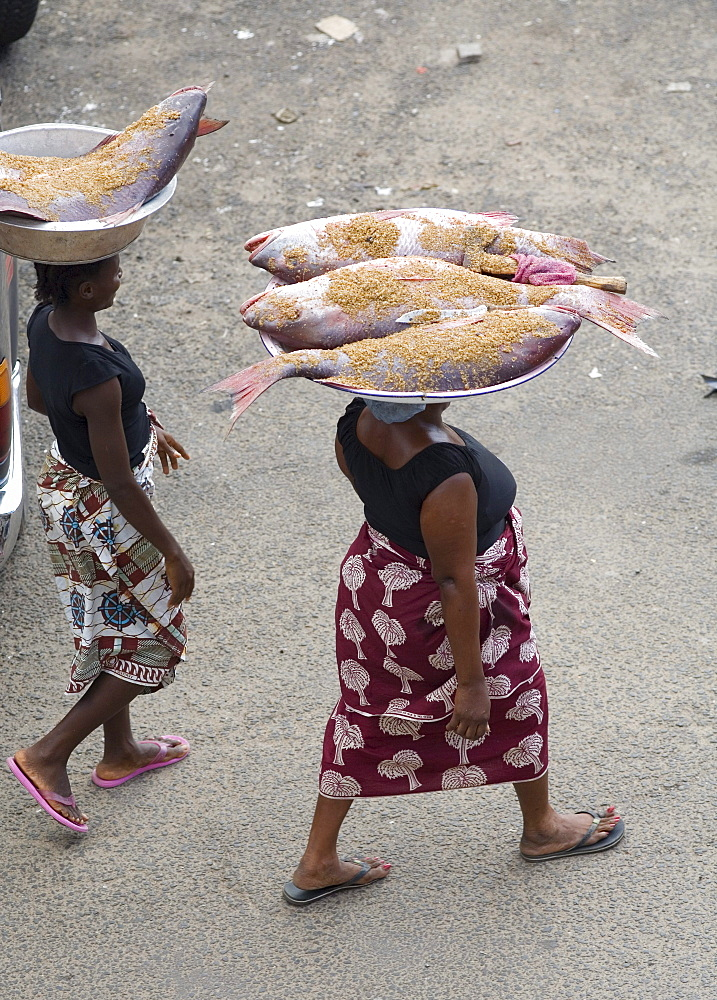 Two Liberian Women carrying large fish on their heads