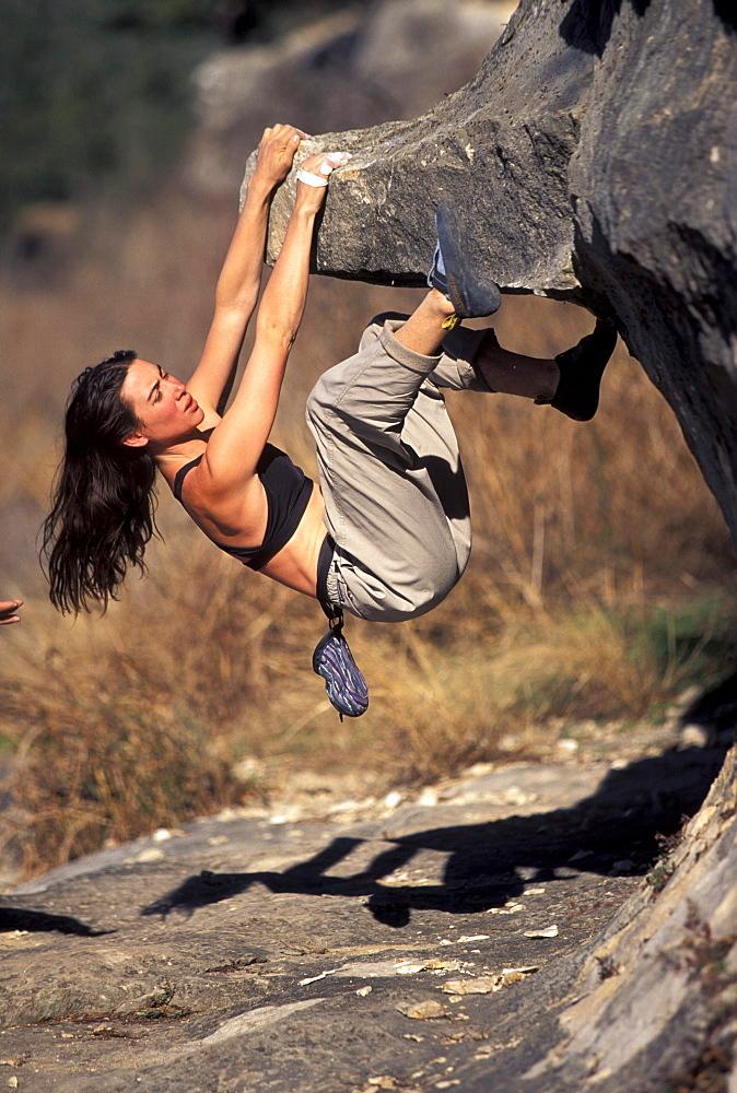 Female climber bouldering on an overhang near San Antonio, Texas.