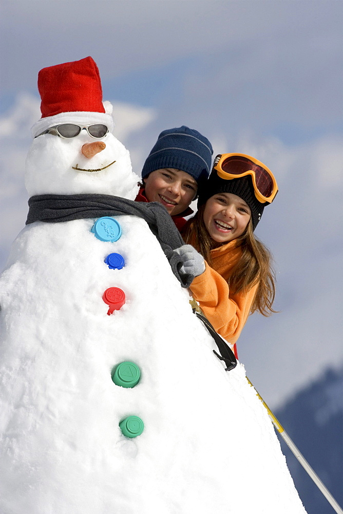 Two children peak out from behind a snowman.