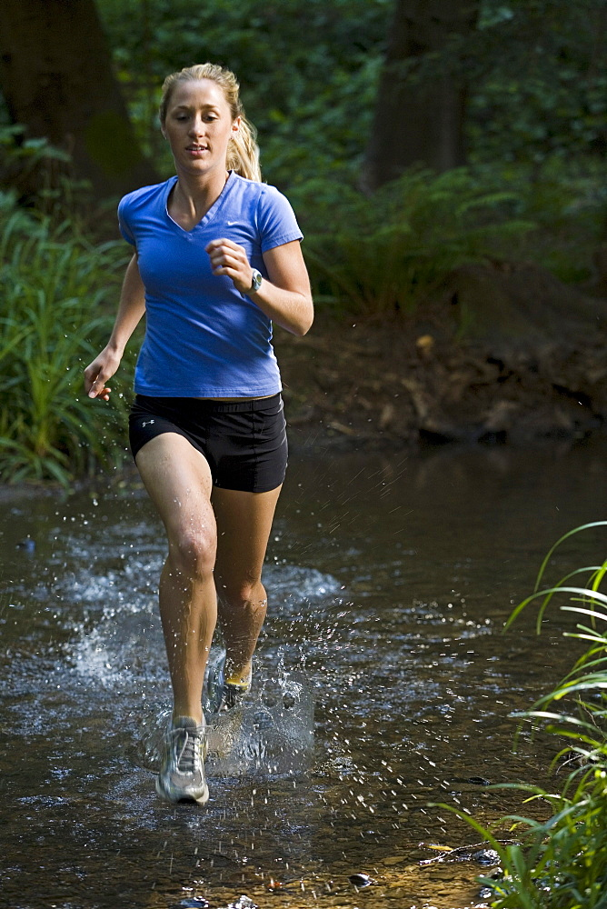 In the darkness of a redwood forest, a runner crosses a stream.