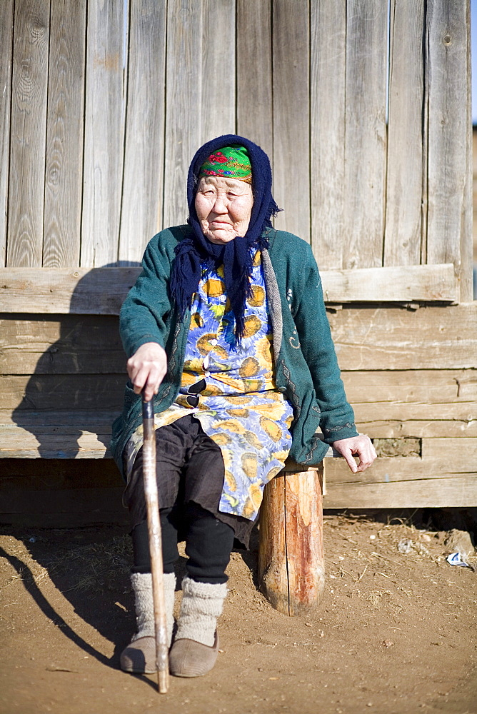A portrait of a local woman in front of her home during the winternon Olkhon Island, Siberia, Russia.