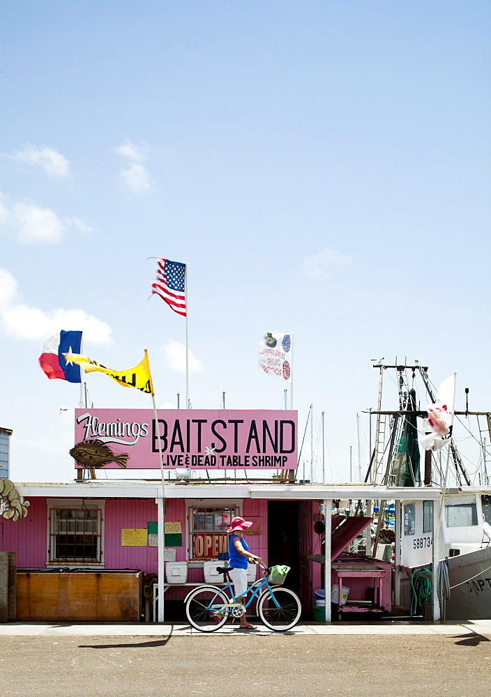 ROCKPORT, TEXAS, USA. A woman walks her bike in front of a bait stand in a small coastal town.