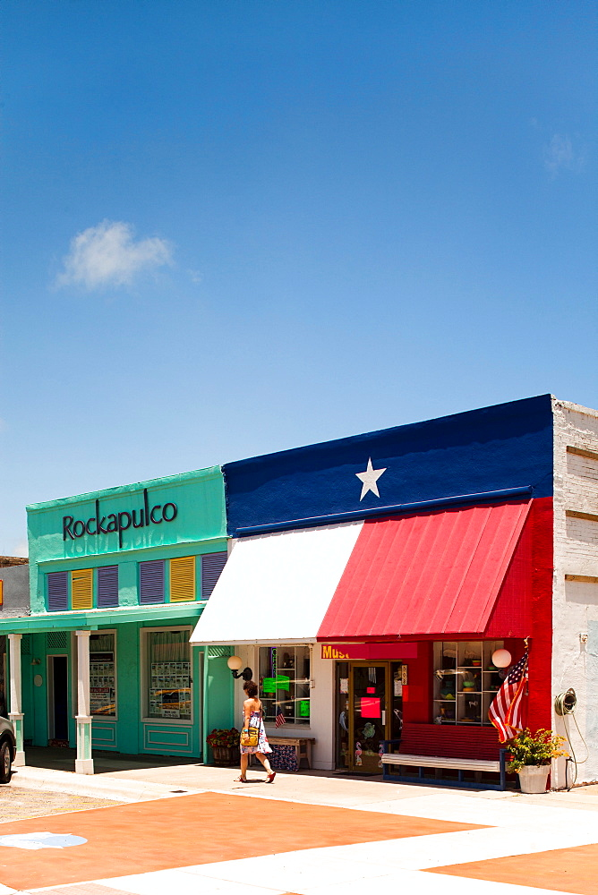 ROCKPORT, TEXAS, USA. A woman walks in front of a store front on a sunny day.