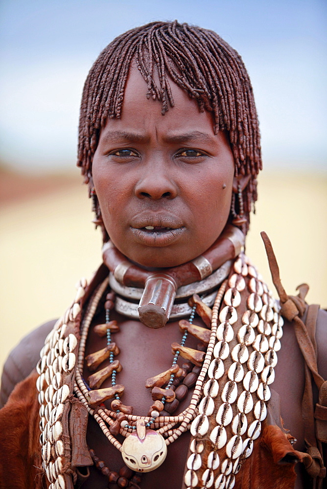 Hamar women are known for practice of body adornment and roll their locks with fat and red ochre (assile) and than twist them into crimson-colored dreads called Goscha, a style that men find attractive.  Dimeka, Omo Valley, Ethiopia, 2010
