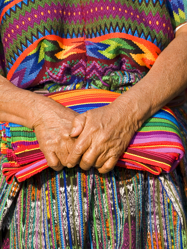 The hands of an indigenous Guatemalan woman holding traditional fabric.