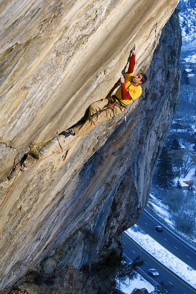 A rock climber in a yellow and red shirt reaching up for a hand hold on a steep and difficult route.