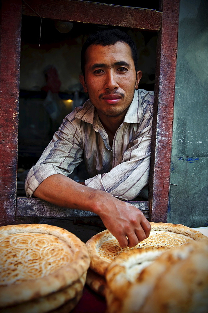 Young Uyghur man selling bread in a window of a traditional Uighur bakery in Kashgar, Xinjiang, China.