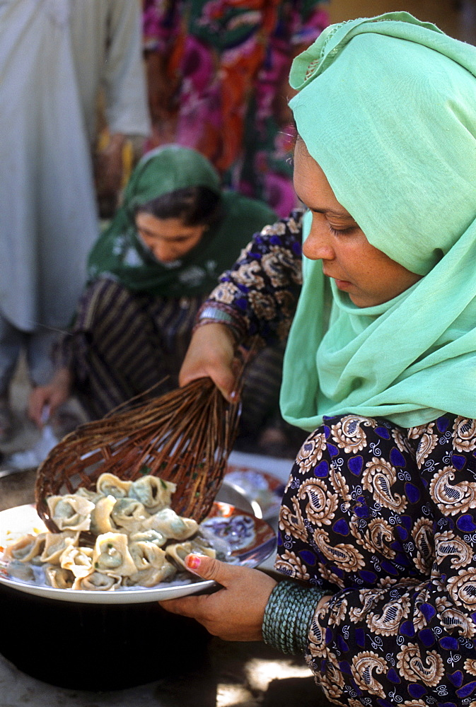 A woman scoops mantu, steamed dumplings stuffed with spiced meat, onto a plate to serve to guests, at a home in Mazar-i Sharif, Afghanistan - 857-55490