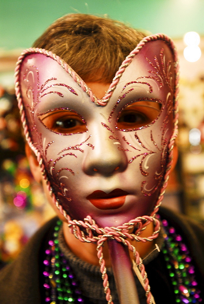Woman holding a Carnival mask over her face.