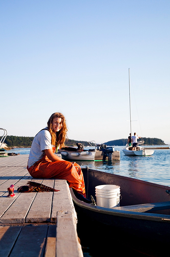 A portrait of a young woman sitting on the edge of a dock with her feet in the boat.