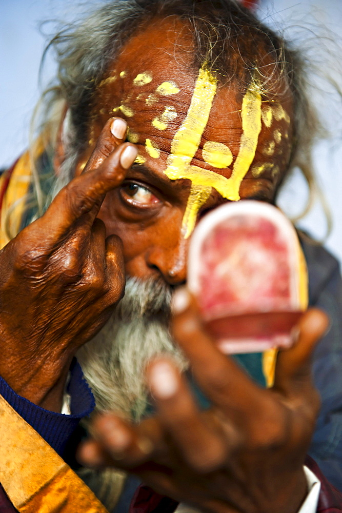 An Indian Sadhu making holy signs on his forhead; Vrindavan, India.