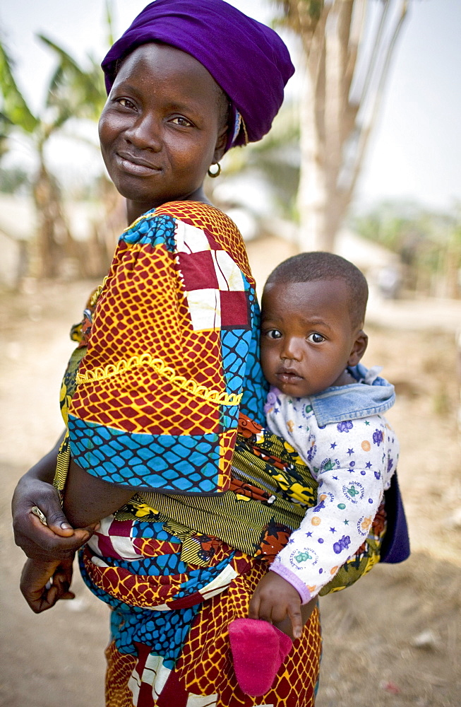 A young woman in the village  of Sakomedu carries her son on her back near the border with Guinea.