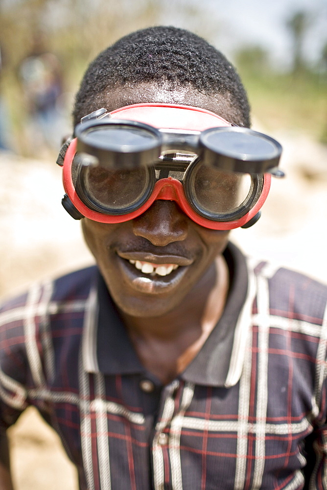Young man wearing protective goggles while breaking rocks working at a gravel pit part of road construction on the  Voinjama - Foya road in Lofa county in Northern Liberia