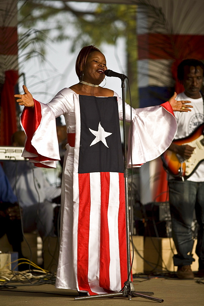 Young Liberian woman wearing a dress with the Liberian flag on it, singing the national anthem during a celebrations in Monrovia, Liberia on January 17th, 2007 marking one year anniversary of President Ellen Johnson Sirleaf coming to power.