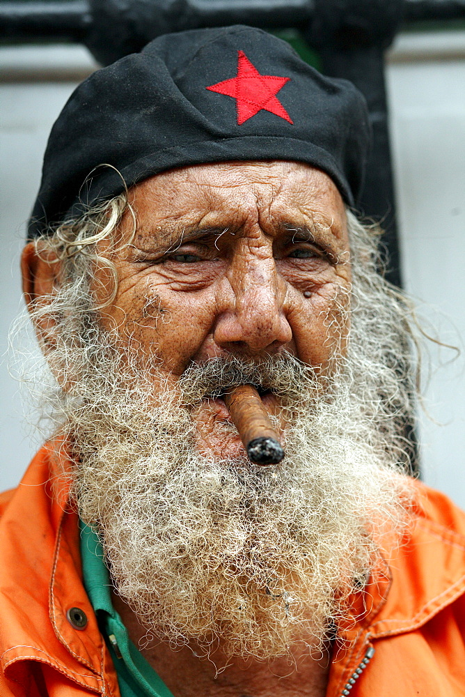 A man with a cigar poses for a portrait near the Plazas de Armas in Havana, Cuba.