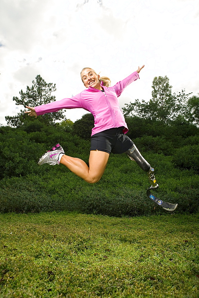 Sarah Reinertsen, the first female amputee to complete the Ironman Triathlon World Championship, jumps in the air for a portrait in Carlsbad, California.