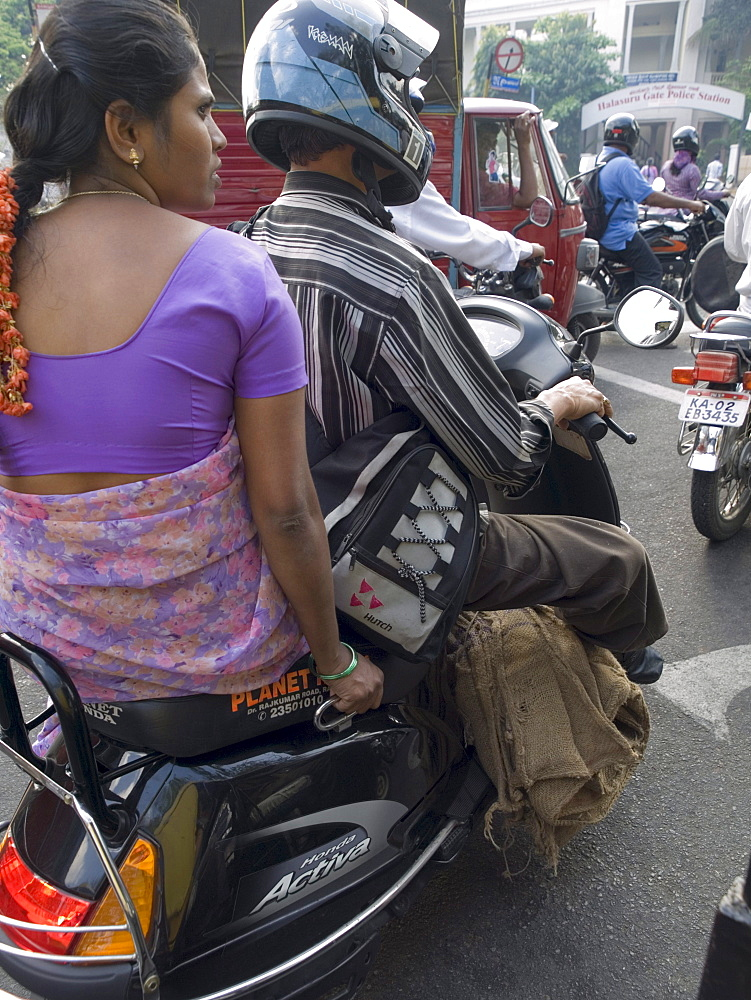 Man and woman on a motorcycle on the road in Bangalore, Karnataka, India