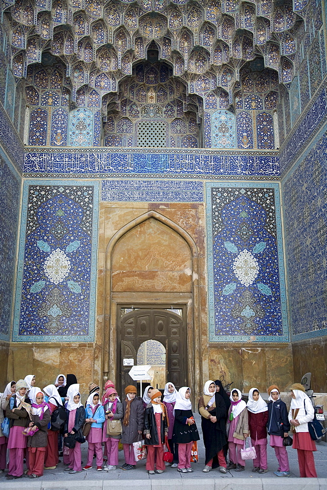 Esfahan, Iran - February, 2008: School girls dressed in pink visiting Imam Mosque. The 17th century mosque was built by Shah Abbas I and is considered one of the most beautiful in world with is blue-tile mosaic design and massive dome.