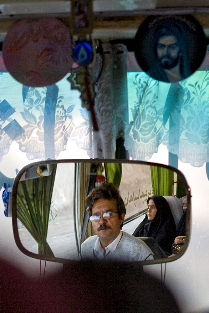 Dasht e Kavir, Iran - February, 2008: Bus driver and female passenger dressed in black reflected in the mirror of a bus enroute through the desert from Esfahan to Khur in Central Iran.