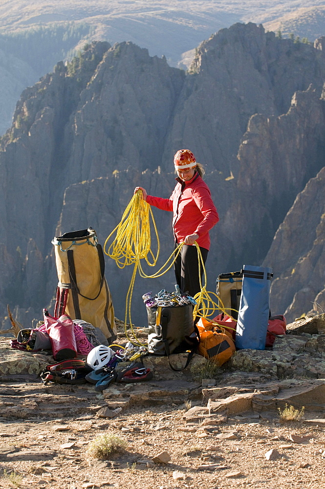 A woman coiling a climbing rope next to multiple bags of gear in the mountains of Crawford, Colorado.