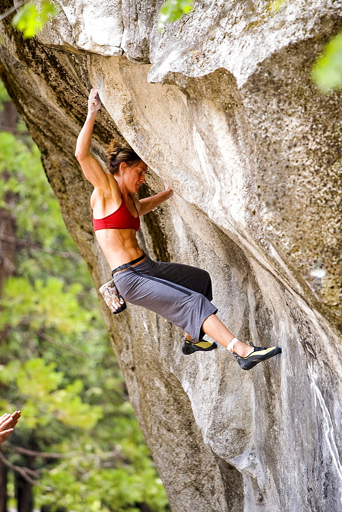 A female rock climber bouldering in Yosemite National Park.