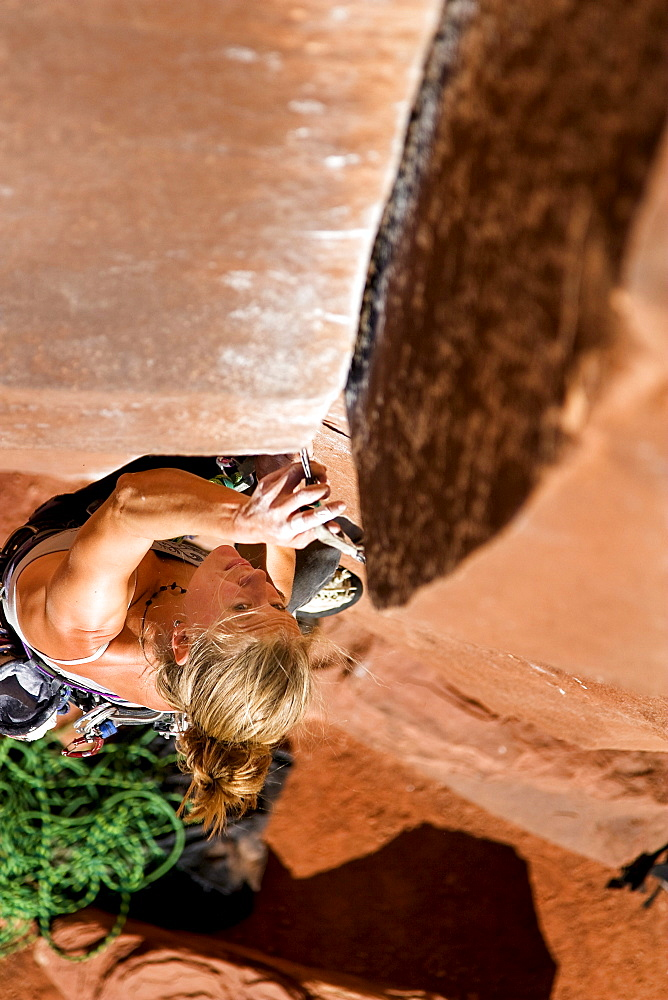 A female rock climber climbs Ruby's Cafe, a classic 5.13 rated climb in Indian Creek, Utah.
