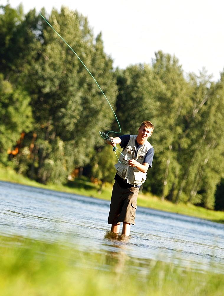 A teenage boy fly fishing in Swan River near Bigfork, Montana.