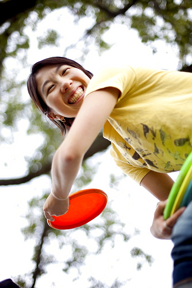 A young Asian-American woman plays flying disk golf in Baltimore, Maryland.