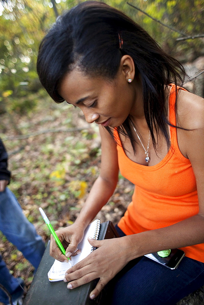 A young woman makes a note in a geocaching logbook in Baltimore, Maryland.