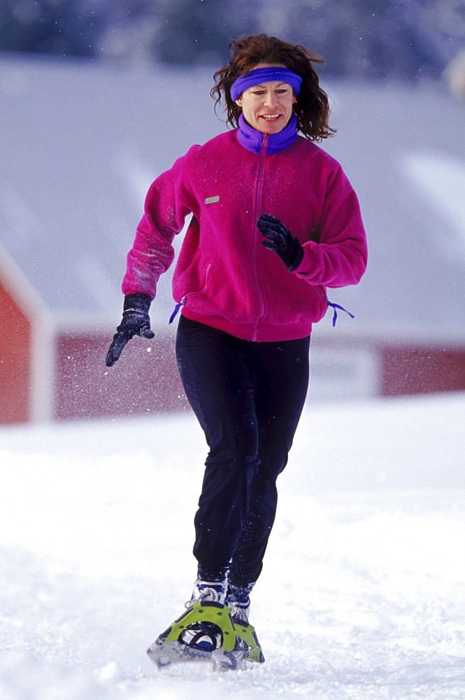 Meril Cray jogs past a barn near Cray's home in Middlesex VT. Cray, an avid jogger during the summer is one of the many people across the country who have taken on the sport of snowshoe running.